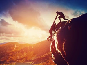 Hikers climbing on rock, mountain at sunset, one of them giving hand and helping to climb. Help, support, assistance in a dangerous situation