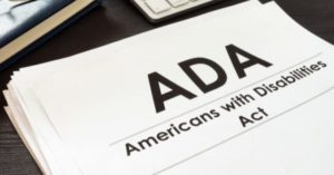 """a paper entitled """"ADA, Americans with disabilities act"""" sits on a desk"""
